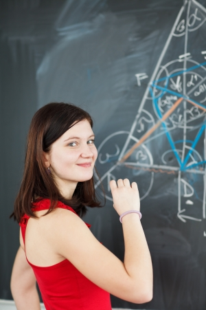 pretty young college student writing on the chalkboard/blackboard during a math class   Stock Photo - 12987917