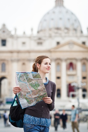 Pretty young female tourist studying a map at St. Peters square in the Vatican City in Rome photo