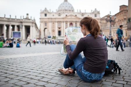 Turística mujer bastante joven estudiando un mapa junto a San Pedro
