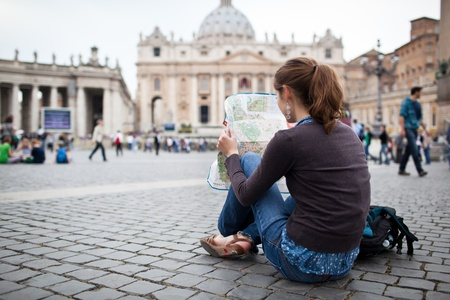 mochila viaje: Tur�stica mujer bastante joven estudiando un mapa junto a San Pedro Foto de archivo