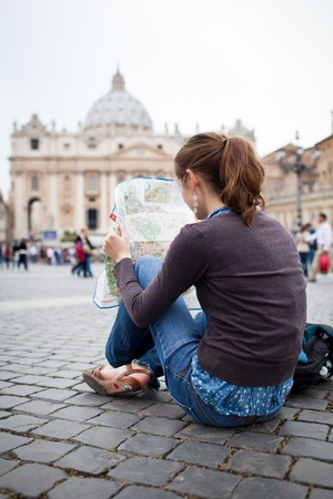 st  peter's basilica pope: Pretty young female tourist studying a map at St. Peters square in the Vatican City in Rome