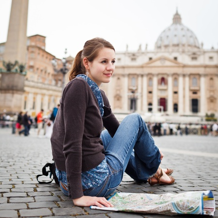 peters: Pretty young female tourist studying a map at St. Peters square in the Vatican City in Rome