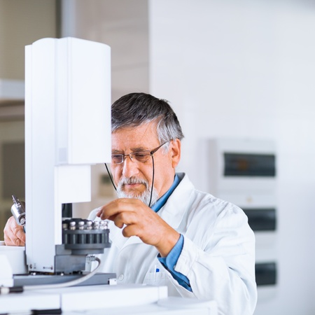 senior male researcher carrying out scientific research in a lab using a gas chromatograph (shallow DOF; color toned image) photo