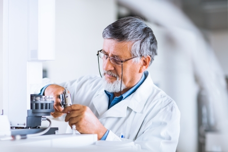 senior male researcher carrying out scientific research in a lab using a gas chromatograph  shallow DOF; color toned image  photo