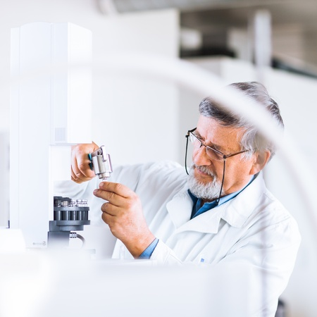 bata de laboratorio: investigador senior masculina llevar a cabo la investigaci�n cient�fica en el laboratorio utilizando un cromat�grafo de gases (DOF bajo; imagen de tonos de color)