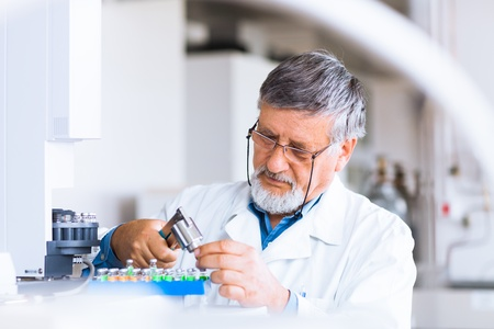 laboratory equipment: senior male researcher carrying out scientific research in a lab using a gas chromatograph  shallow DOF; color toned image  Stock Photo