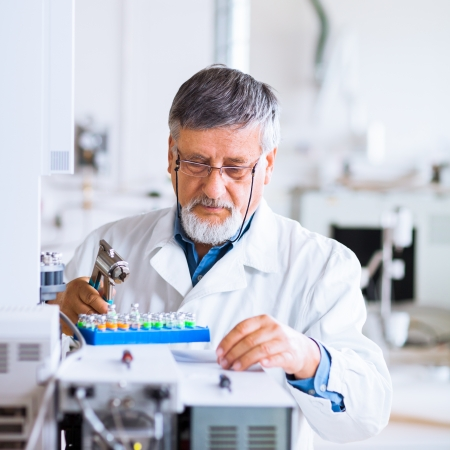 scientific experiment: senior male researcher carrying out scientific research in a lab using a gas chromatograph (shallow DOF; color toned image)