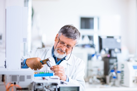 laboratory equipment: senior male researcher carrying out scientific research in a lab using a gas chromatograph (shallow DOF; color toned image)