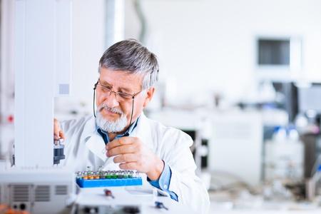 investigador senior masculina llevar a cabo la investigación científica en el laboratorio utilizando un cromatógrafo de gases DOF ??someras, la imagen tonos de color Foto de archivo