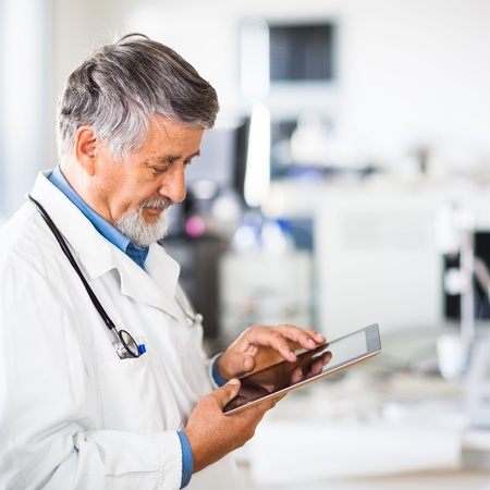 professions: Senior doctor using his tablet computer at work (color toned image) Stock Photo