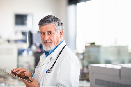 Senior doctor using his tablet computer at work (color toned image) Stock Photo
