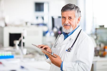 cirujano: M�dico jefe usando su Tablet PC en la imagen de trabajo de color entonado