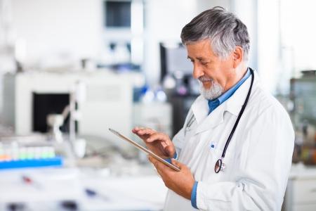 patient arzt: Oberarzt mit seinem Tablet-Computer bei der Arbeit Farbe get�ntes Bild
