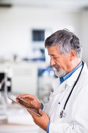 consulting room: Senior doctor using his tablet computer at work (color toned image) Stock Photo