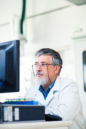 Senior researcher using a computer in the lab while working on an experiment  color toned image  photo
