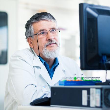 Ricercatore senior utilizzando un computer in laboratorio mentre si lavora su un esperimento (immagine a colori tonica)