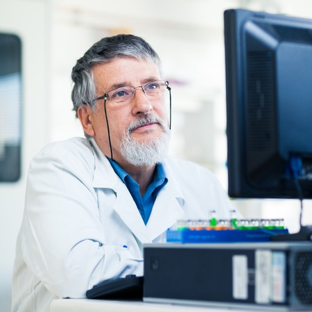 Senior researcher using a computer in the lab while working on an experiment (color toned image) Stock Photo - 13444708