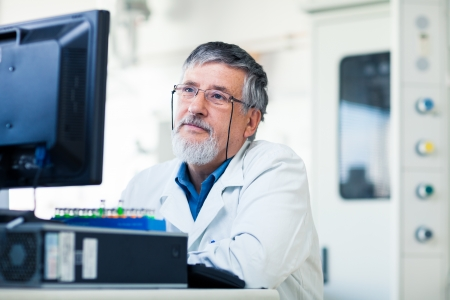Senior researcher using a computer in the lab while working on an experiment (color toned image)