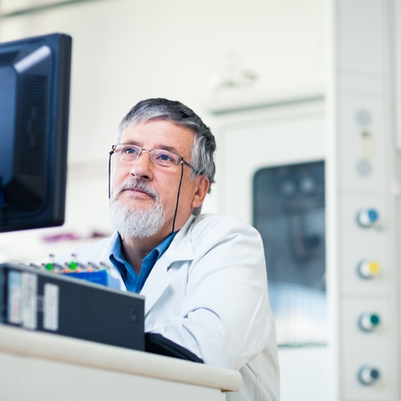 Senior researcher using a computer in the lab while working on an experiment (color toned image) Stock Photo - 13444586