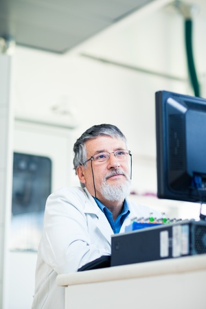 Senior researcher using a computer in the lab while working on an experiment (color toned image) Stock Photo - 13444740