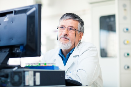 phisician: Senior researcher using a computer in the lab while working on an experiment  color toned image