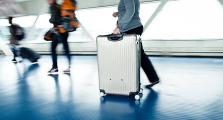 viajero: Aeropuerto de punta: la gente con sus maletas caminando por un pasillo (imagen en movimiento borrosa, color de la imagen tono) Editorial