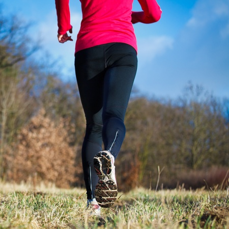 Jogging outdoors in a meadow (shallow dof, focus on the running shoe) photo