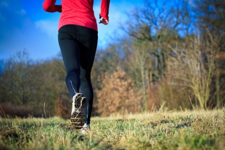 girl in sportswear: Jogging outdoors in a meadow (shallow dof, focus on the running shoe)