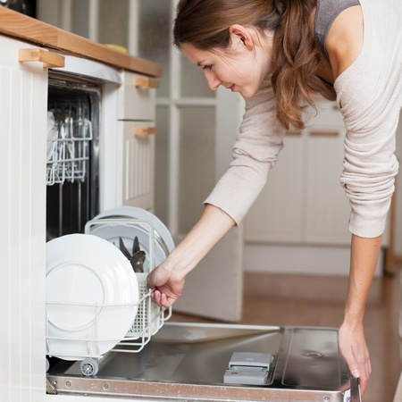 chores: Housework: young woman putting dishes in the dishwasher Stock Photo