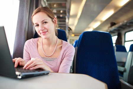 Young woman using her laptop computer while on the train (shallow DOF; color toned image) photo