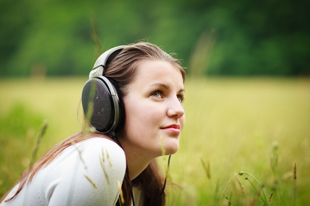 headphone: portrait of a pretty young woman listening to music on her mp3 player outdoors (daydreaming)