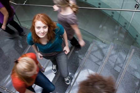 adulthood: At the universitycollege - Students rushing up and down a busy stairway - confident pretty young female student looking upwards (color toned image)