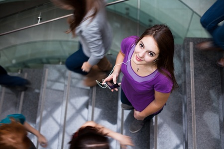 At the universitycollege - Students rushing up and down a busy stairway - confident pretty young female student looking upwards while listening to music on her mp3 player (color toned image) photo