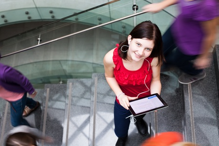 movement people: Pretty young student on the campus, holding a tablet computer while standing in the middle of a busy stairway, looking upwards