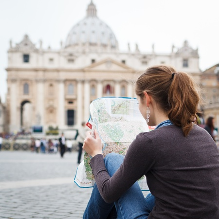 st  peter's square: Pretty young female tourist studying a map at St. Peters square in the Vatican City in Rome