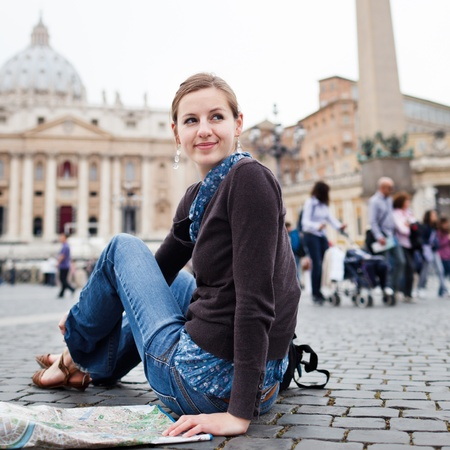 traveller: Pretty young female tourist studying a map at St. Peters square in the Vatican City in Rome