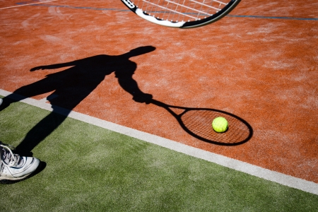 shadow of a tennis player in action on a tennis court (conceptual image with a tennis ball lying on the court and the shadow of the player positioned in a way he seems to be playing it) photo