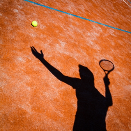 serve: shadow of a tennis player in action on a tennis court (conceptual image with a tennis ball lying on the court and the shadow of the player positioned in a way he seems to be playing it)