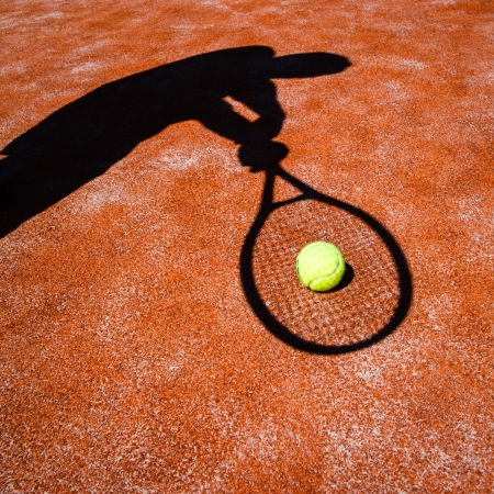 backhand: shadow of a tennis player in action on a tennis court (conceptual image with a tennis ball lying on the court and the shadow of the player positioned in a way he seems to be playing it)