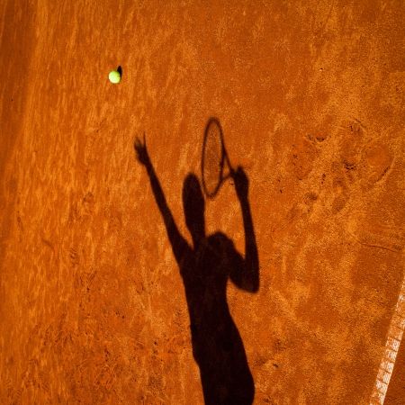 tennis clay: shadow of a tennis player in action on a tennis court (conceptual image with a tennis ball lying on the court and the shadow of the player positioned in a way he seems to be playing it)