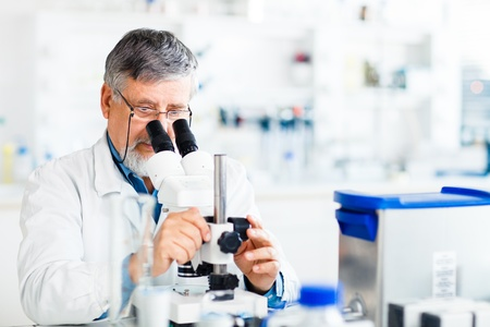 scientific equipment: senior male researcher carrying out scientific research in a lab using a microscope (shallow DOF; color toned image) Stock Photo