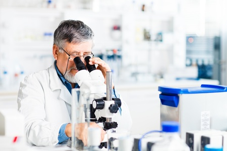 chromatograph: senior male researcher carrying out scientific research in a lab using a microscope (shallow DOF; color toned image) Stock Photo