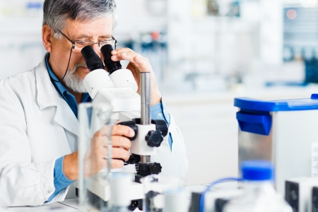 research worker: senior male researcher carrying out scientific research in a lab using a microscope (shallow DOF; color toned image) Stock Photo