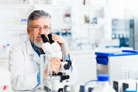 research study: senior male researcher carrying out scientific research in a lab using a microscope (shallow DOF; color toned image) Stock Photo