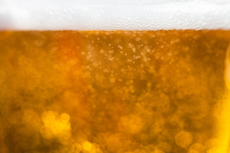 Golden macro background: gas bubbles in beer at shallow DOF against sunlight Stock Photo - 13926564