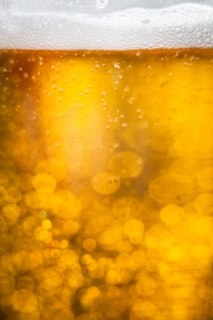 Golden macro background: gas bubbles in beer at shallow DOF against sunlight photo