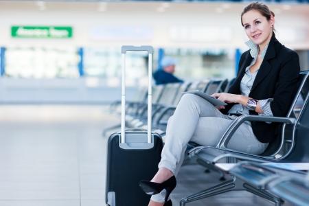 gente aeropuerto: Hembra joven pasajero en el aeropuerto, usando su Tablet PC a la espera de su vuelo (imagen a color entonado)