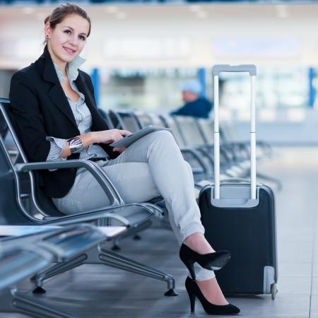 gente aeropuerto: Pasajeros joven mujer en el aeropuerto, usando su Tablet PC a la espera de su vuelo (imagen a color entonado)