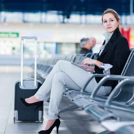 young businesswoman: Young female passenger at the airport, using her tablet computer while waiting for her flight (color toned image)
