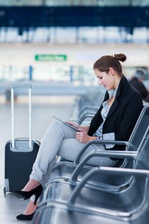 Jonge vrouwelijke passagier op de luchthaven, met behulp van haar tablet-computer tijdens het wachten op haar vlucht (kleur getinte afbeelding)